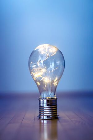 Photo for LED light bulb is lying on the wooden floor. Symbol for ideas and innovation. Copy space.  - Royalty Free Image