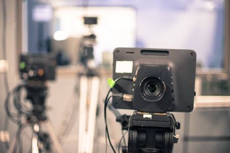 Photo for Lens of a film camera in an television broadcasting studio, spotlights and equipment - Royalty Free Image