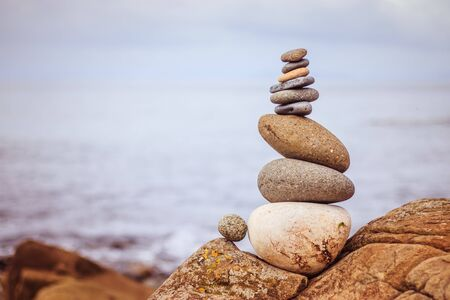Photo for Close up picture of a stone cairn outdoors. Ocean in the blurry background - Royalty Free Image