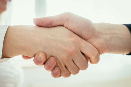 Photo pour Man and woman are shaking hands, close up image, concept for human relationships - image libre de droit