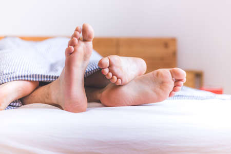 Photo pour Close up a couples uncovered feet sleeping in bed, morning - image libre de droit