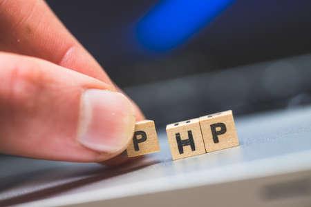 "Photo pour Wooden cubes with the letters ""PHP"" are lying on a laptop - image libre de droit"