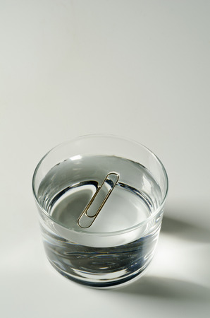 Photo for Physics. Surface tension. A paper clip floating on water. - Royalty Free Image