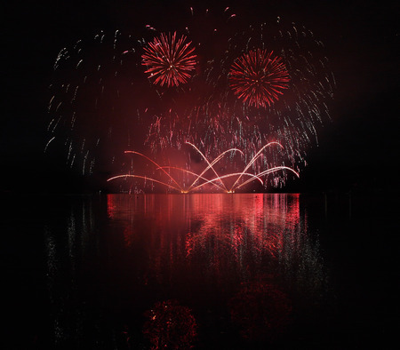 Colorful fireworks with reflection on lake and night sky in background.