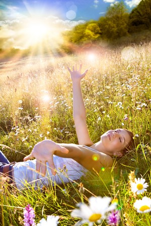 Photo for beautiful young girl lying in a sunset marguerite meadow - Royalty Free Image