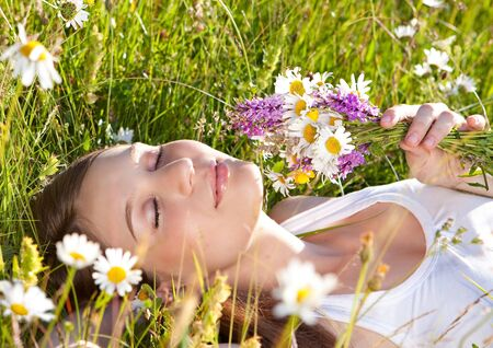 beautiful young girl lying in a marguerite meadowの写真素材