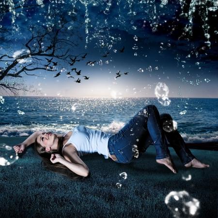 beautiful girl lying in the rain on a meadow in the evening