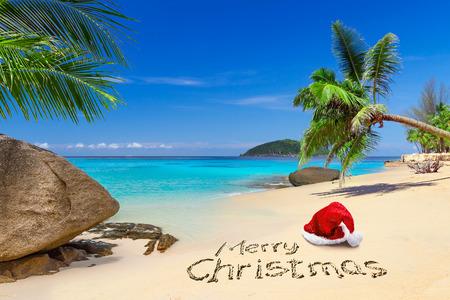 Foto de Merry Christmas greeting with santa hat on the tropical beach - Imagen libre de derechos