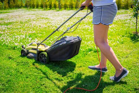 Photo pour Woman cutting grass in her yard with lawn mower. - image libre de droit