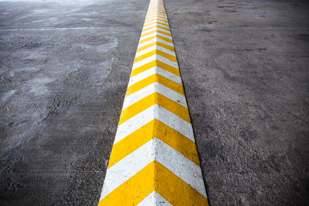 A yellow stripe speed ramp on concrete road.