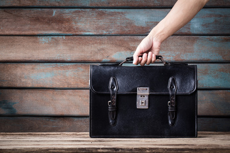Foto de vintage classic of hand man holding leather Schoolbag on wooden background. - Imagen libre de derechos