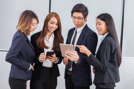 Photo pour Young business people is standing concentrate on iPad and smile with white background - image libre de droit