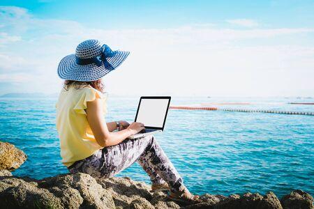 Photo pour Business woman sitting by the sea with laptop computer - image libre de droit