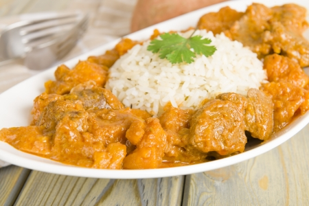 Lamb and sweet potato peanut stew served with white rice  Caribbean and West African dish