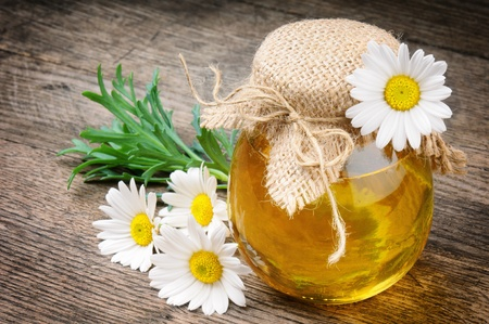 Glass pot of honey with daisies on wooden table