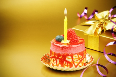 Photo pour Colorful birthday cake with candle on golden background - image libre de droit