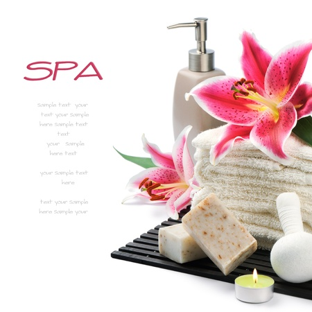 Spa setting with towels, organic soap and lily isolated on white