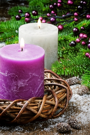 Burning candles on festive Christmas background with ornaments
