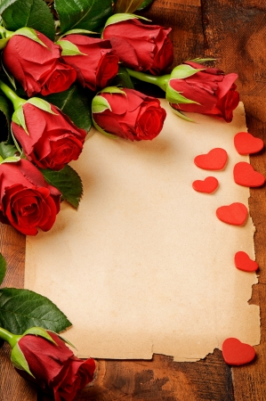 Frame with red roses and vintage paper on wooden table