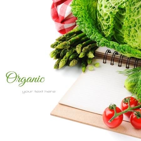Fresh organic vegetables and cooking book isolated over white