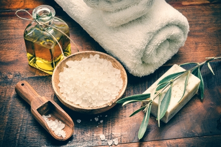 Spa setting with natural olive soap and sea salt on wooden table