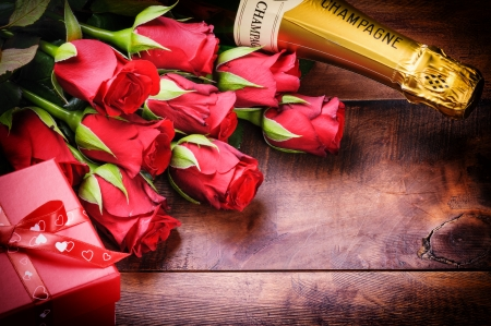 Valentine's setting with red roses, champagne and gift on old wood background