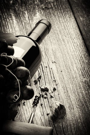 Photo pour Bottle of red wine with fresh grape and corkscrew. Black and white concept - image libre de droit