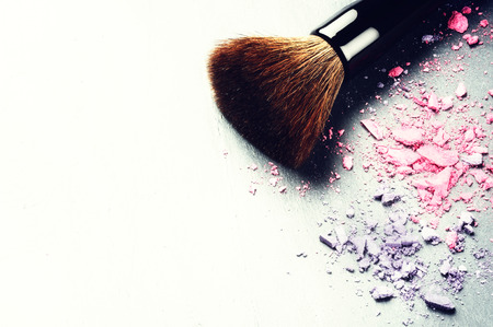 Makeup brush and crushed eyeshadows on light backgroundの写真素材