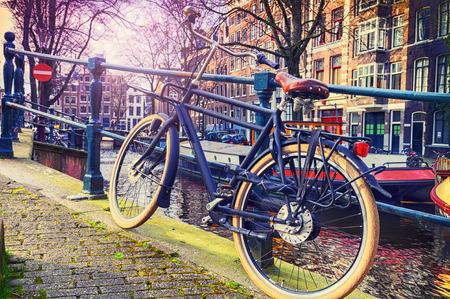 Foto de Old bicycle standing next to canal. Amsterdam cityscape - Imagen libre de derechos