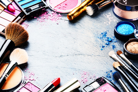 Colorful frame with various makeup products on dark backgroundの写真素材