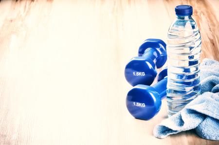 Fitness concept with dumbbells and water bottle. After workout setting