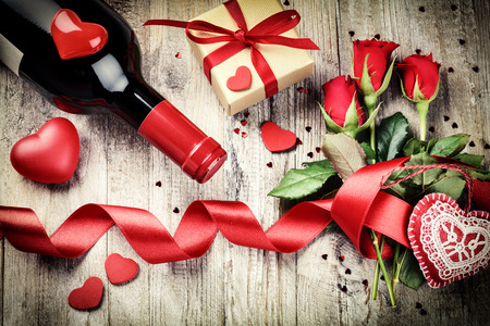 Photo pour St Valentine's setting with red roses bouquet, present and red wine bottle. Copy space - image libre de droit