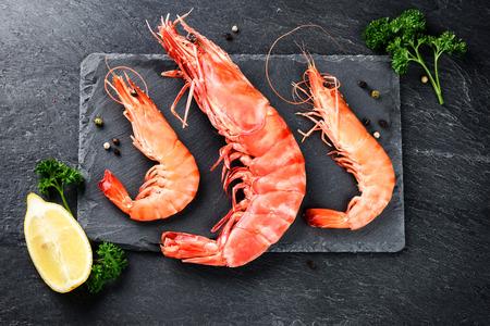 Foto de Fine selection of jumbo shrimps for dinner on stone plate. Food background - Imagen libre de derechos