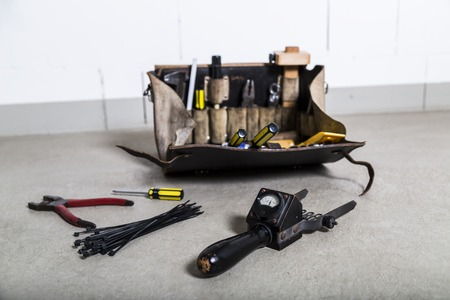 Box with electrician tools on leather background