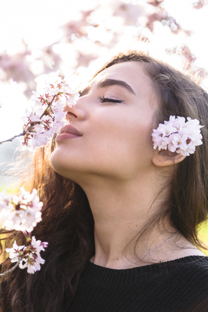 Girl with pleasure smells branch with flowers