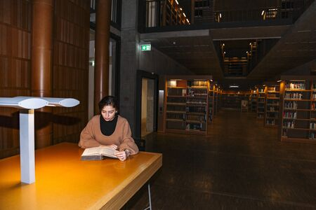 Photo pour Girl reads book by light of lamp sitting at table - image libre de droit