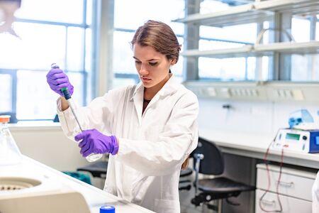 Photo pour Girl researcher drips test liquid into test tube - image libre de droit