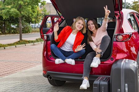 Photo pour Two girls in trunk of red car posing for camera - image libre de droit