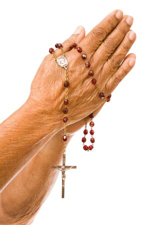 An old asian woman holds her hands in prayer with a rosary