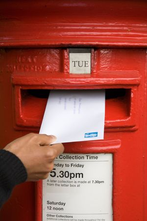 A woman posts a letter in a traditional British red post box