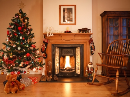 Traditional living room with a cosy open fire, adorned with christmas decorations and a tree. [Note: Picture above fireplace is photographers own work]