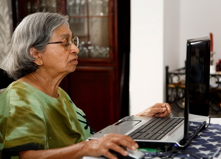 Elderly Asian Indian woman uses a laptop computer at home