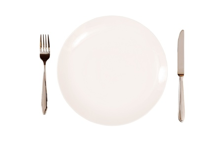 White plate with knife and fork isolated on a white background.