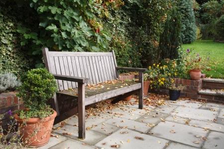 Garden bench on a traditional flagstone patio in autumn / fall