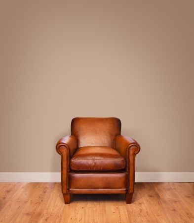 Leather armchair on a wooden floor against a plain background wall with lots of copyspace  The wall has a clipping path