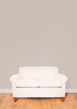 Modern cream sofa against a blank wall with lots of space for text