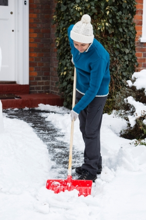 Person shovelling snow off driveway outside her house