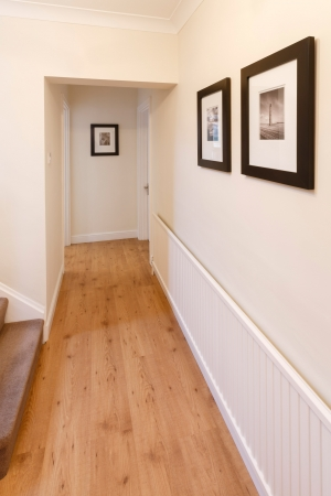 Hallway in a home with wooden floor and pictures on the wall