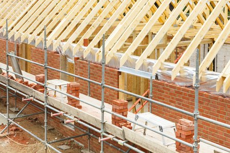 Foto per Construction site in UK with a house built from brick and timber, featuring brickwork, roof trusses and scaffolding - Immagine Royalty Free