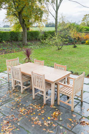Photo for Large back garden in UK countryside in autumn, with wooden furniture on a garden patio terrace - Royalty Free Image